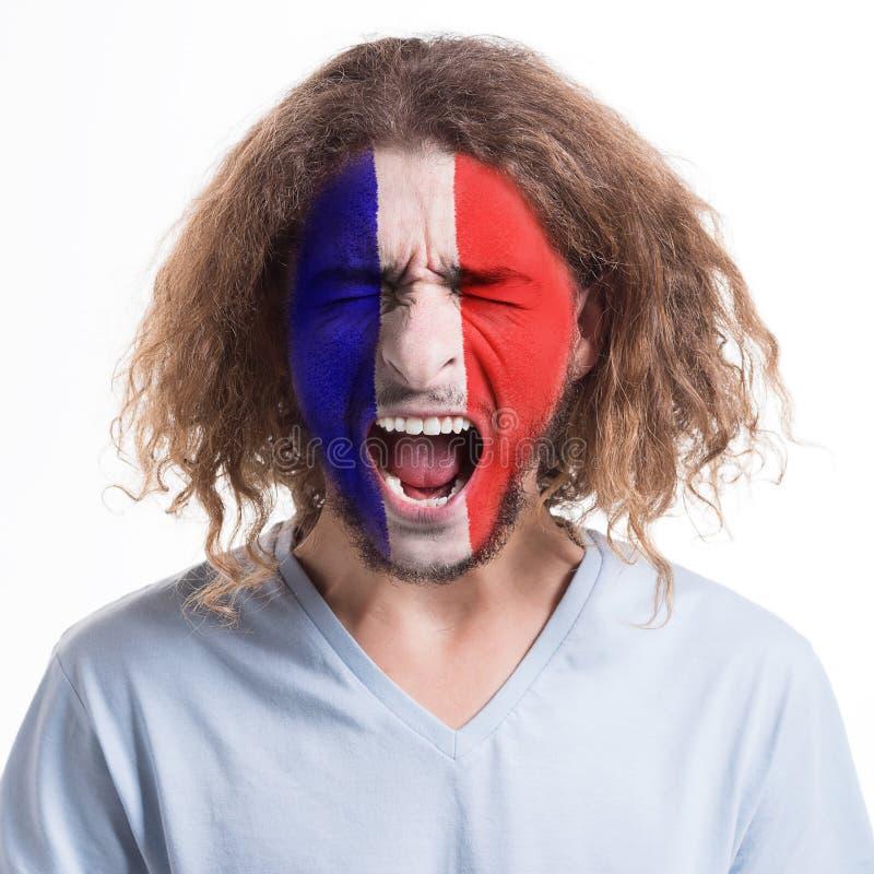 De jonge mens met de vlag van Frankrijk schilderde op zijn gezicht stock fotografie
