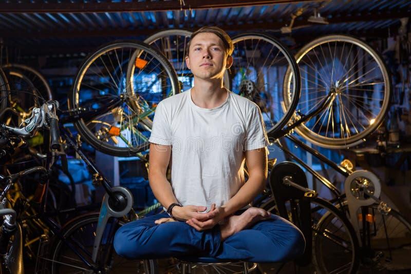 De jonge mens oefent yoga in garage met vele erachter fietsen uit royalty-vrije stock afbeeldingen
