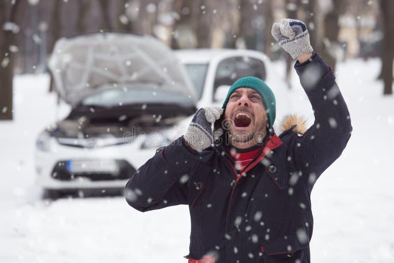 De jonge mens is onder spanning omdat zijn opgesplitste auto op sneeuw DA stock foto's