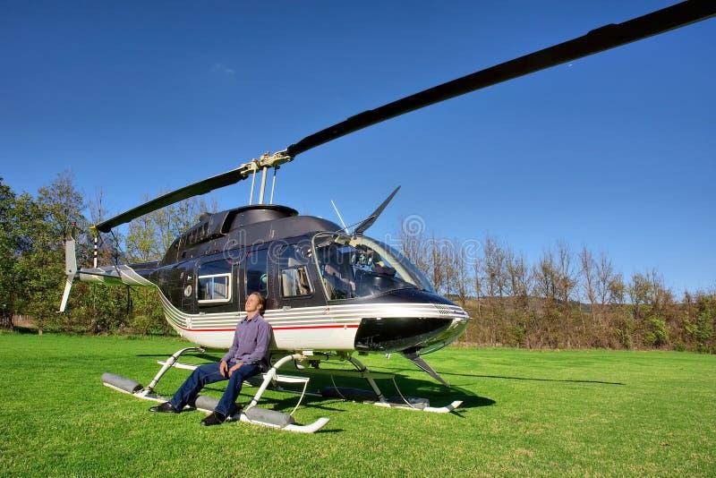 De jonge mens ontspant naast kleine helikopter royalty-vrije stock foto