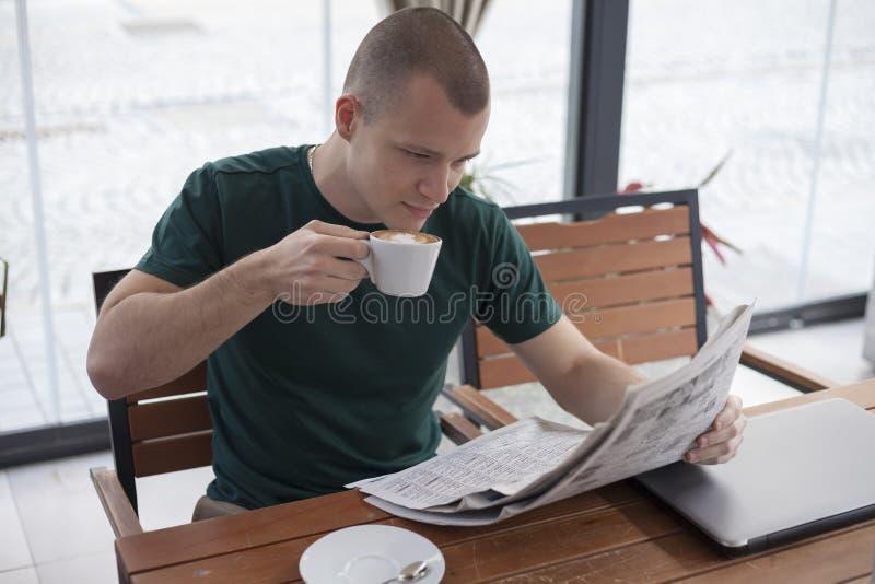 De jonge mens ontspant tijdens een onderbreking op het werk Leest het recentste nieuws stock fotografie