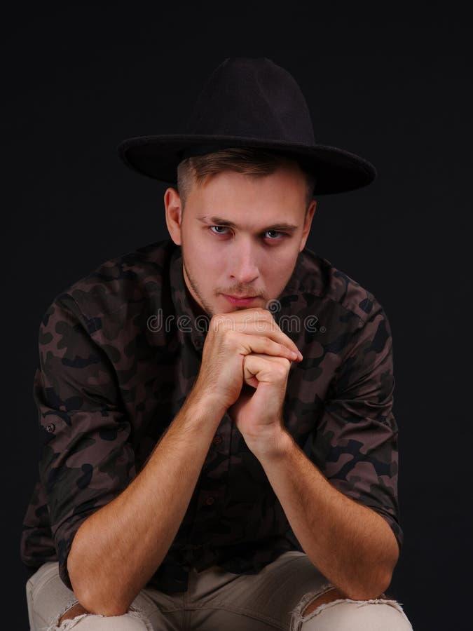 De jonge mens op een zwarte achtergrond met een hoed bekijkt de camera royalty-vrije stock fotografie