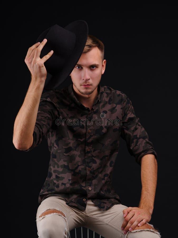 De jonge mens op een zwarte achtergrond stijgt zijn hoed op royalty-vrije stock foto