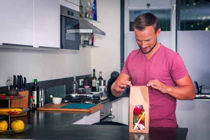 De jonge mens opent een pakket van verse ingrediënten om een gezond diner te maken royalty-vrije stock foto's