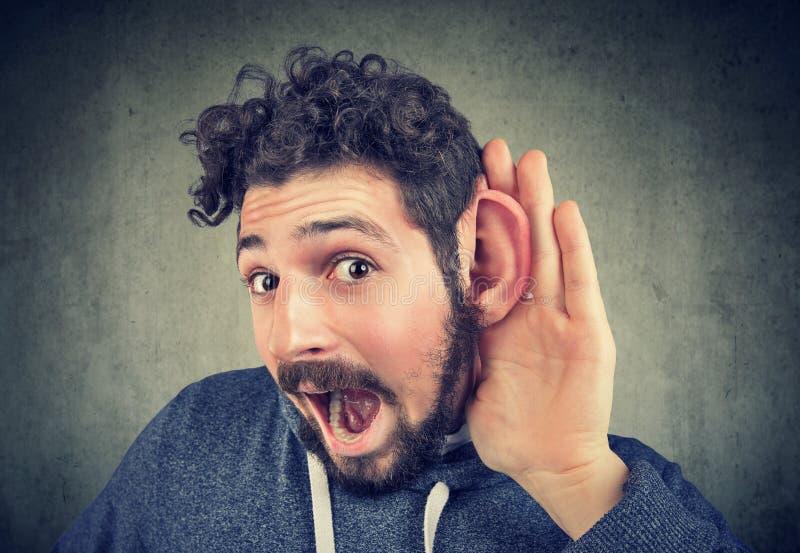 De jonge mens probeert zorgvuldig te luisteren stock foto