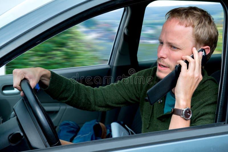 De jonge mens roept binnen de auto stock afbeelding
