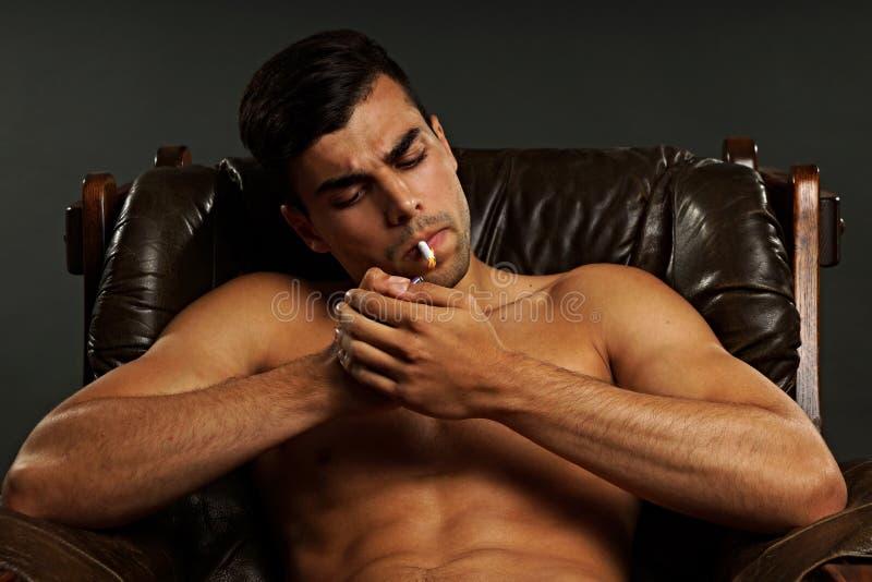 De jonge mens rookt als voorzitter stock foto's