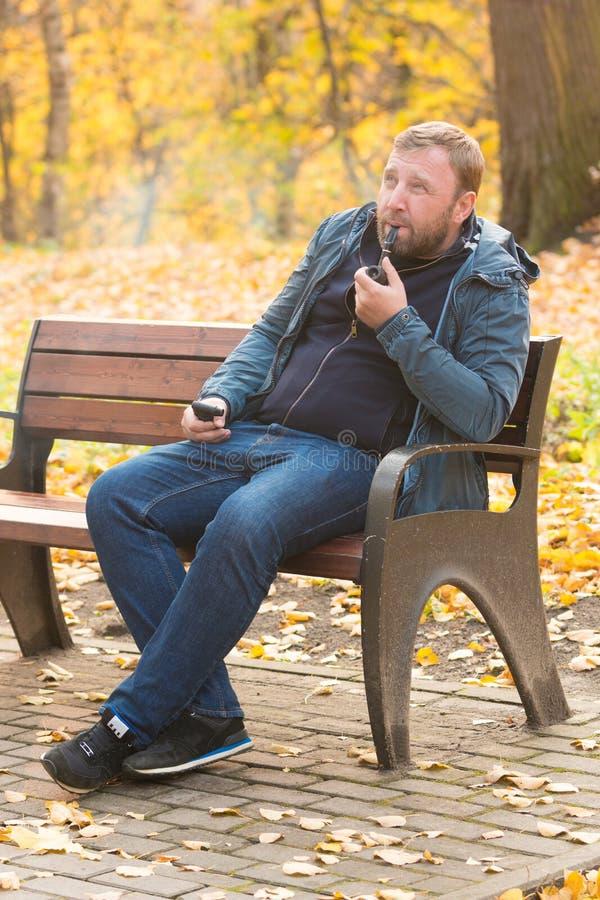 De jonge mens rookt pijp in park royalty-vrije stock foto's