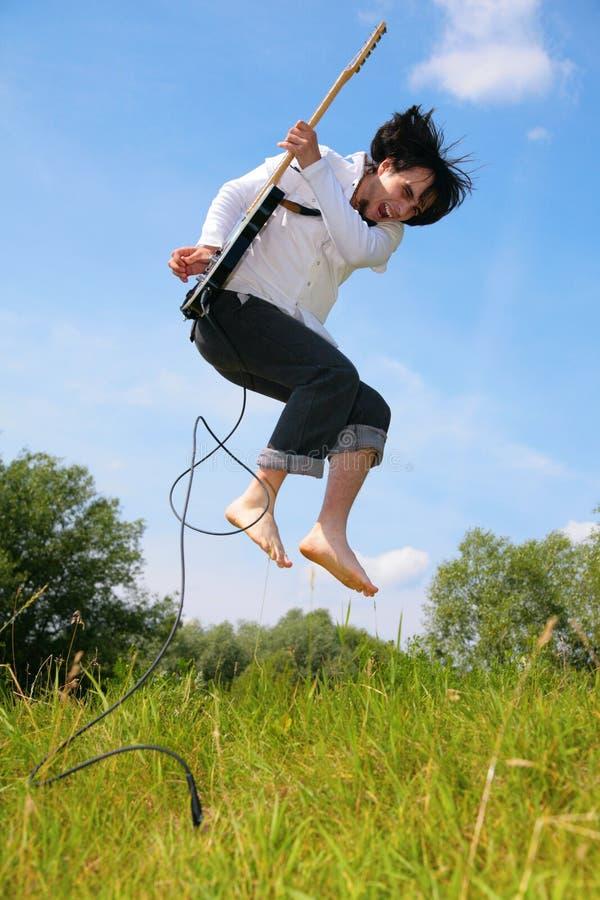 De jonge mens springt met gitaar op gras royalty-vrije stock fotografie