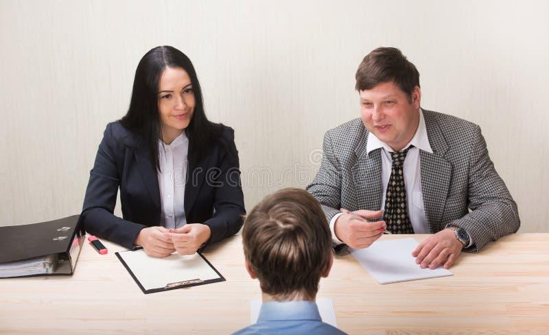 De jonge mens tijdens baangesprek en de leden van managemen stock afbeelding