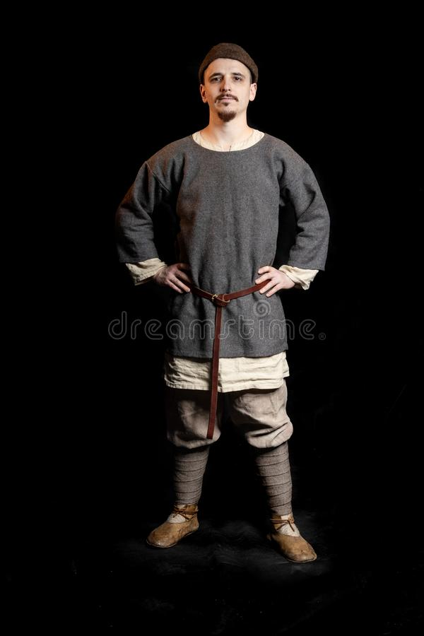 de jonge mens in toevallige grijze kleren en een hoed van Viking Age kijkt ernstig, overhandigt op heupen stock foto