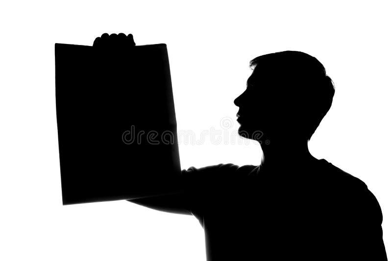 De jonge mens toont een krant, een blad van document - silhouet royalty-vrije stock afbeelding
