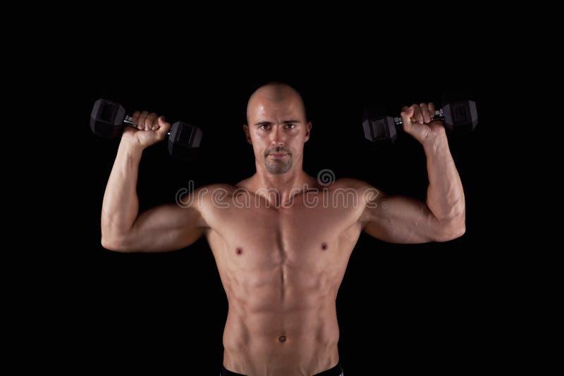 De jonge mens van de spier met dumbells royalty-vrije stock afbeelding