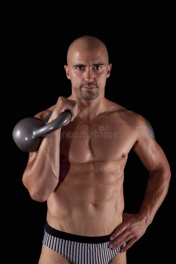 De jonge mens van de spier met kettlebells stock foto
