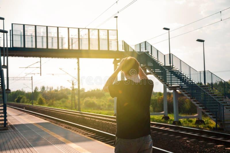 De jonge mens van de rug, die zijn handen op het hoofd van vermaak houden aangezien zijn trein heeft departured vroeger De mens i royalty-vrije stock afbeelding