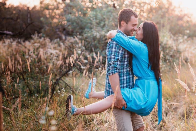 De jonge mens vervoert in zijn wapens een jong aantrekkelijk meisje in een park stock foto