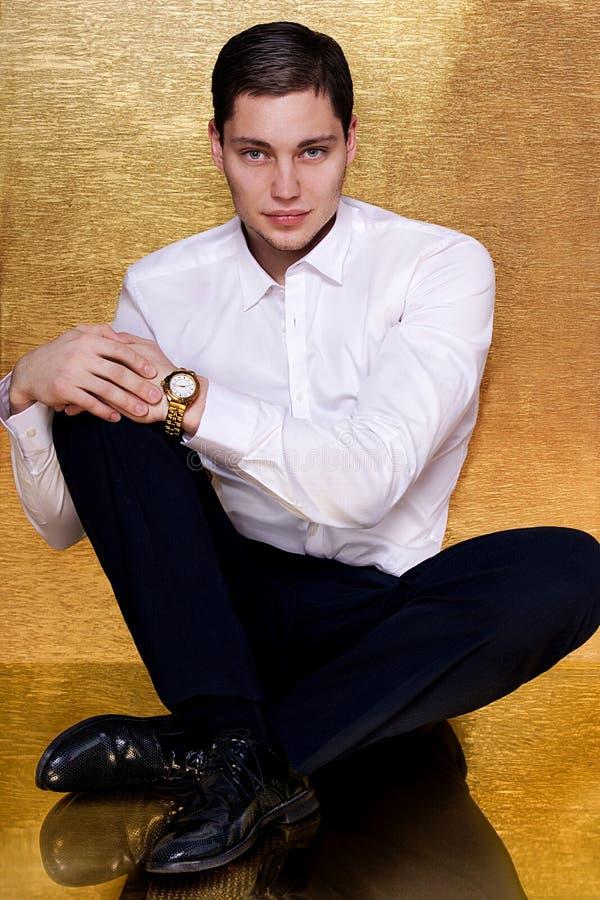De jonge mens in wit overhemd maait gouden horloge stock afbeelding