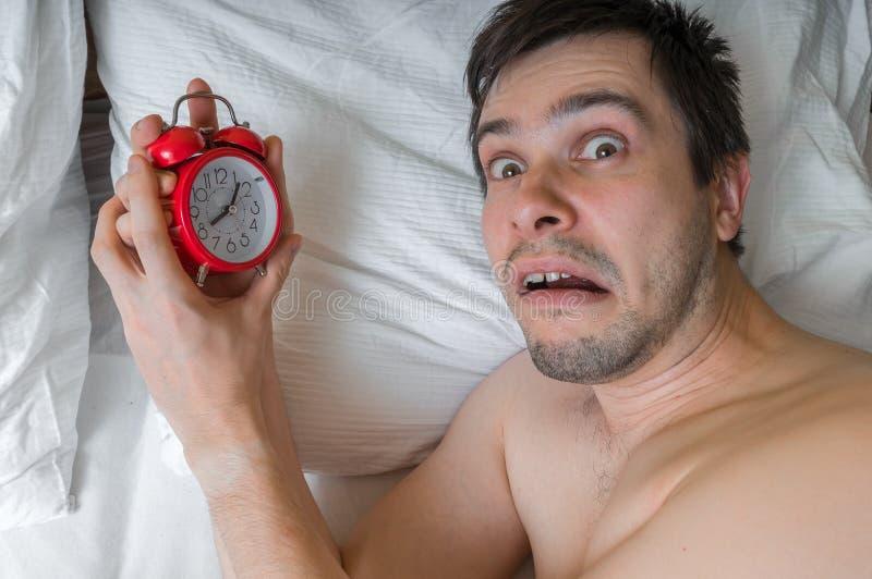 De jonge mens wordt beklemtoond en geschokt Hij verslaapt zich en miste iets royalty-vrije stock foto