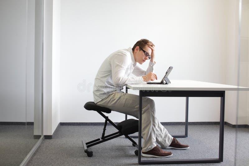 De jonge mens wordt gebogen over zijn tablet. Slechte zittingshouding op het werk stock foto's