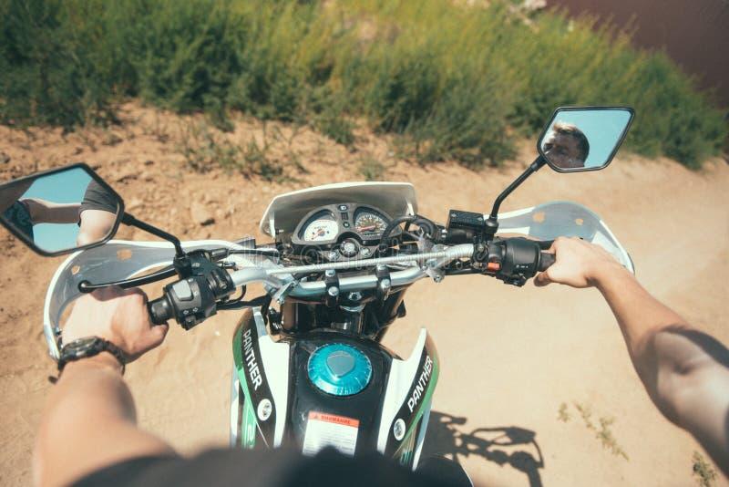 De jonge mens zit achter het wiel van een mening van de motorfiets eerste-persoon royalty-vrije stock fotografie