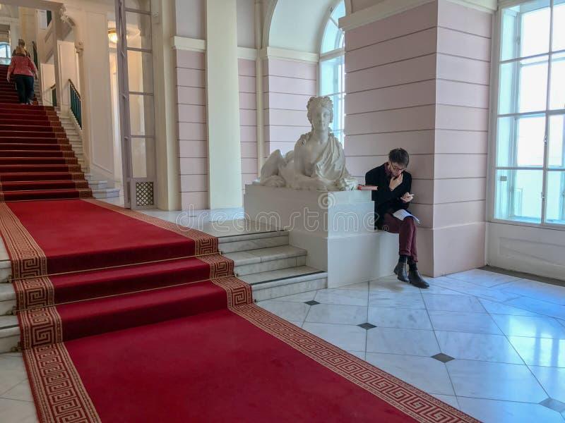 De jonge mens zit door standbeeld in Albertina Museum, Wenen royalty-vrije stock foto