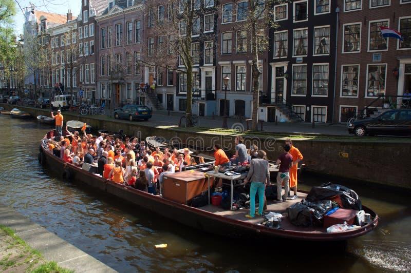 De jonge mensen berijden op de kanaalschepen in Amsterdam stock fotografie