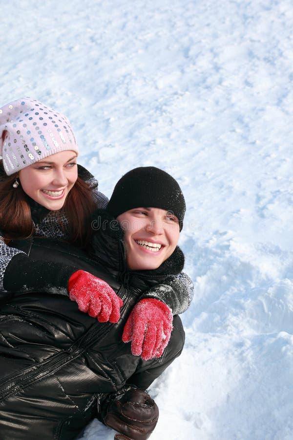 De jonge mensen liggen zijdelings op sneeuw royalty-vrije stock fotografie