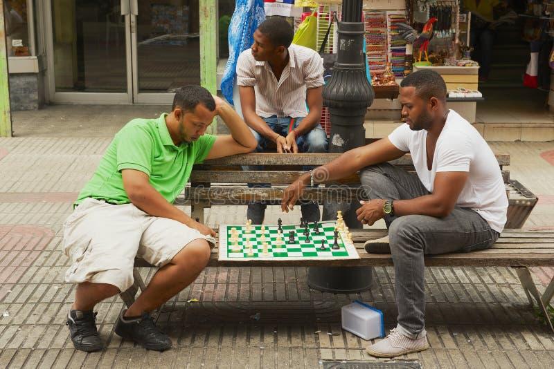 De jonge mensen spelen schaakzitting bij een bank bij de voetstraat in Santo Domingo, Dominicaanse Republiek royalty-vrije stock afbeelding