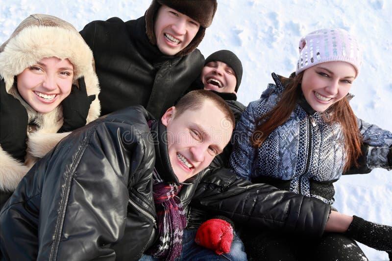 De jonge mensen tegen de winterdag liggen op sneeuw royalty-vrije stock fotografie