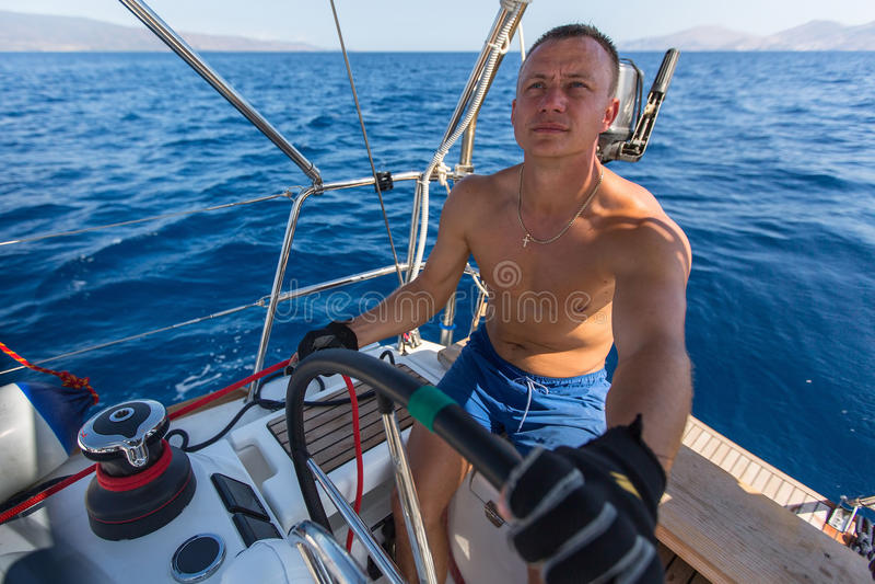 De jonge mensenkapitein stuurt boot varend jacht op de oceaan Sport stock afbeelding