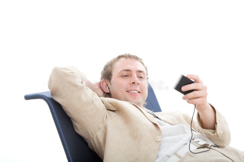 De jonge mensenrust als voorzitter en luistert digitale speler stock afbeelding