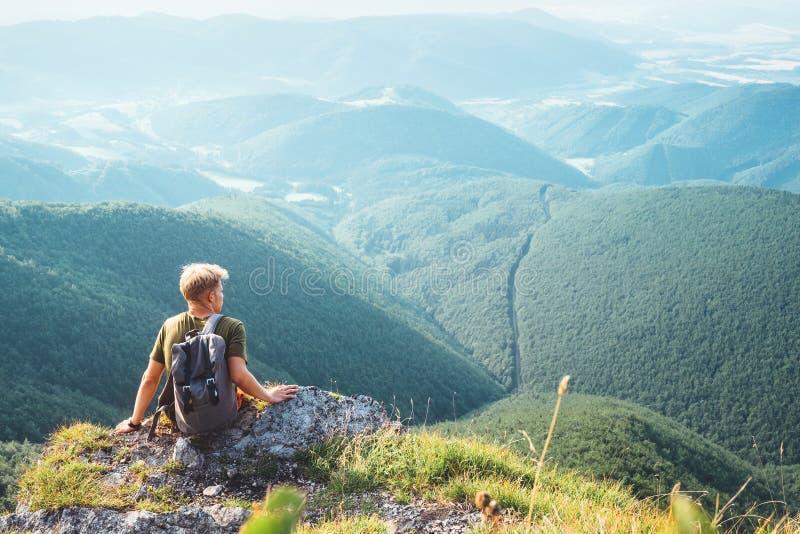 De jonge mensentoerist backpacker zit op bovenkant op heuvel met mooi royalty-vrije stock afbeelding
