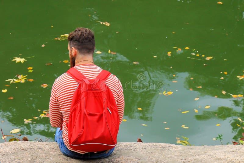 De jonge mensentoerist met een rode rugzak zit op een meer op de herfstdag Gele gevallen bladerenvlotter op het water in bladdali royalty-vrije stock fotografie