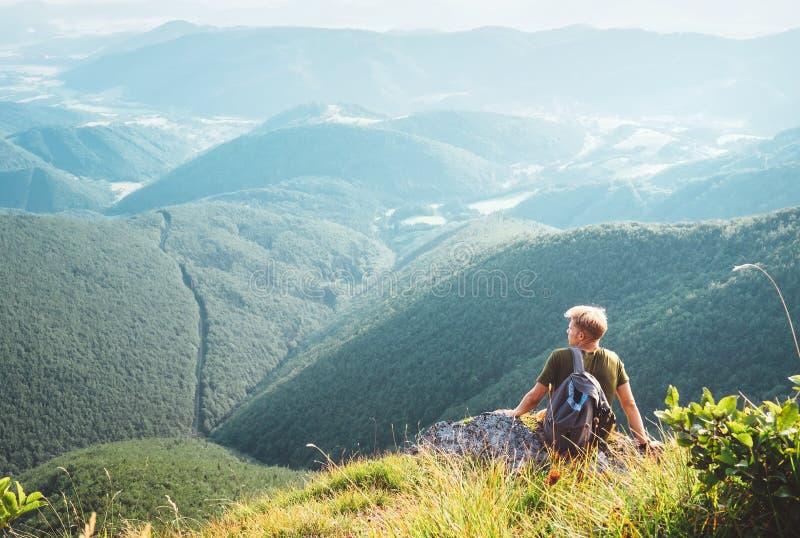 De jonge mensentoerist zit op bovenkant op heuvel met mooie valleipano stock foto's