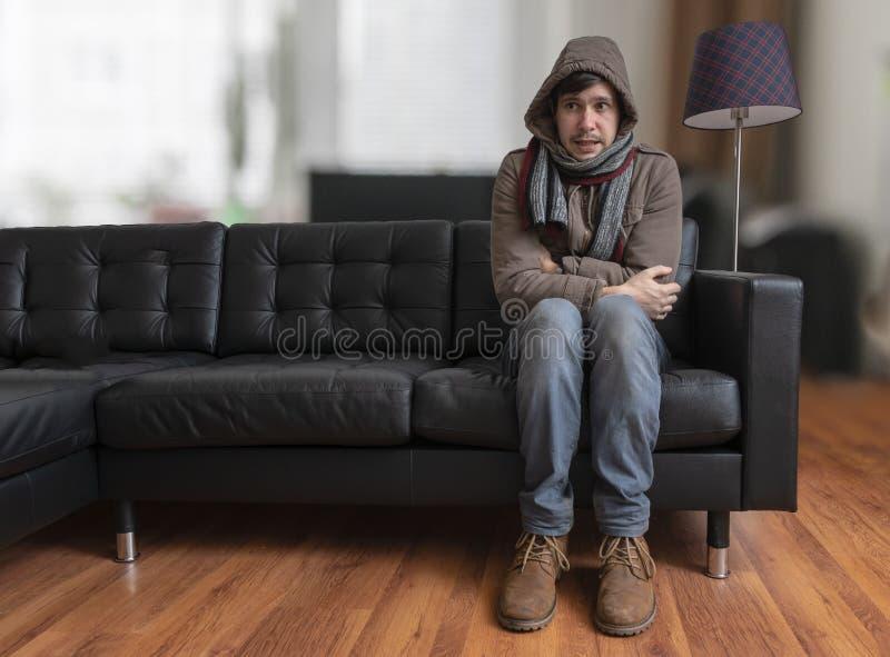 De jonge mensenzitting op laag voelt thuis koud royalty-vrije stock foto
