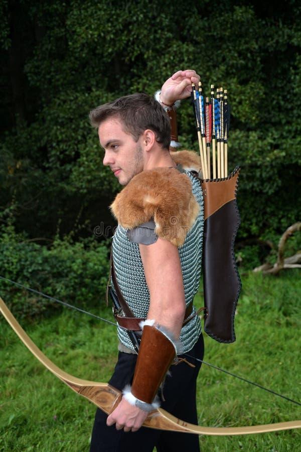 De jonge Middeleeuwse schutter met kettingsoverhemd bereikt voor pijl, met in hand boog royalty-vrije stock foto's