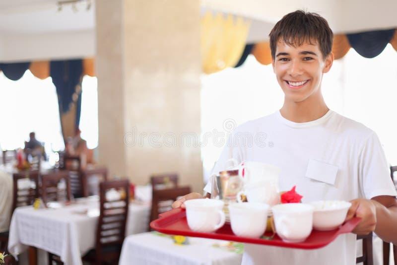 De jonge minzame kelner houdt dienblad bij restauran royalty-vrije stock foto