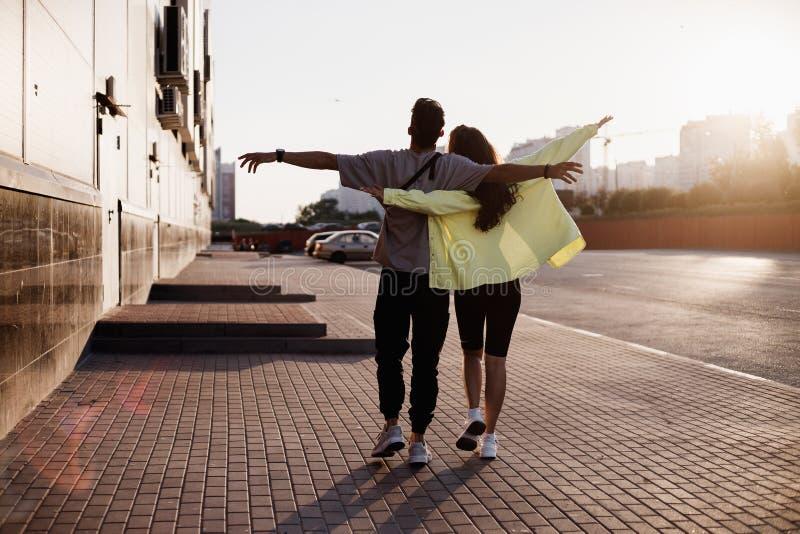 De jonge modieuze kerel en het meisje lopen samen op het vierkant voor parkeren naast het gebouw op de zonsondergang royalty-vrije stock afbeeldingen