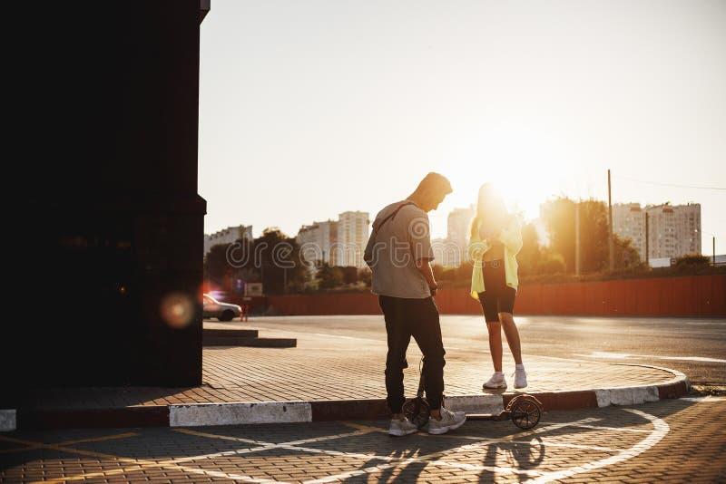 De jonge modieuze kerel met autoped en het meisje verenigen zich op het vierkant voor parkeren op de zonnige dag stock foto's