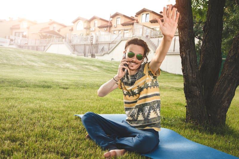 De jonge modieuze knappe glimlachende mens met zonnebril zit op gras, rust en spreekt op de telefoon golven zijn hand het welkom  royalty-vrije stock afbeeldingen