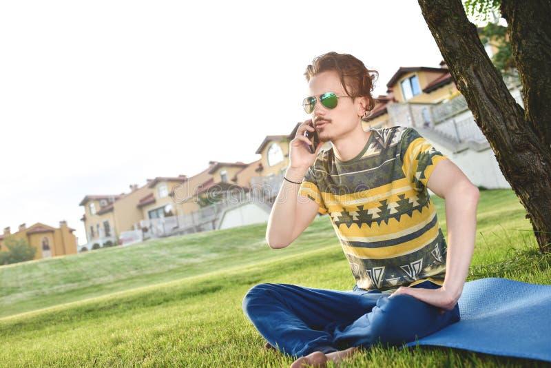 De jonge modieuze knappe mens zit op gras en spreekt op de telefoon die in het park rusten Het nemen van een onderbreking stock foto