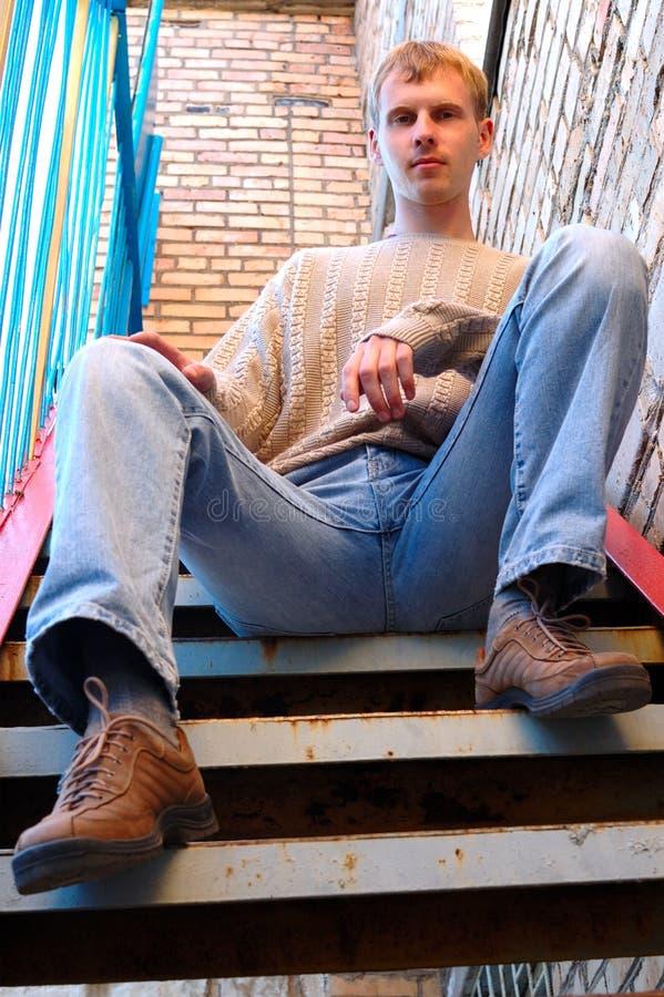 De jonge modieuze mens zit op treden dichtbij bakstenen muur. royalty-vrije stock foto's