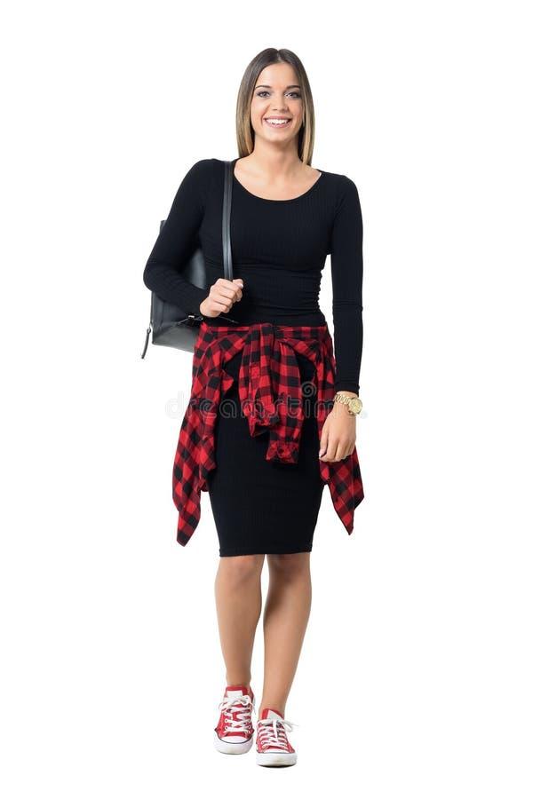 De jonge modieuze mooie dragende zak van het studentenmeisje over schouder die en camera het glimlachen lopen bekijken stock afbeelding