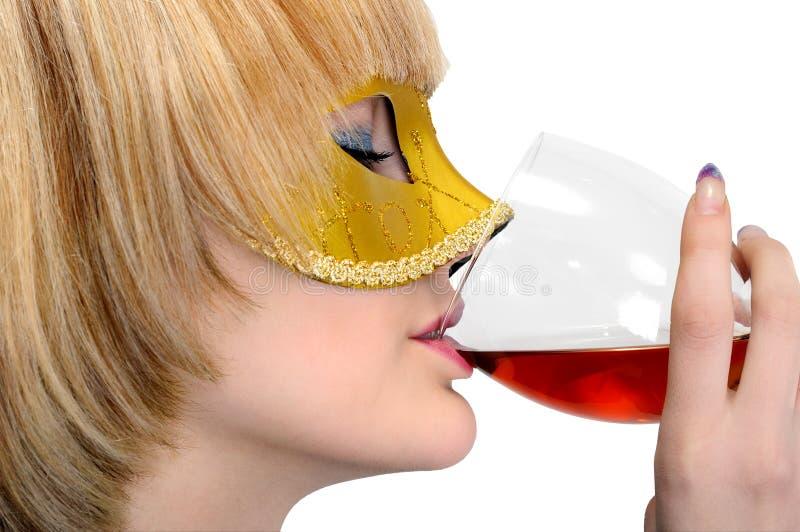 De jonge modieuze vrouw in Carnaval-masker drinkt rode wijn stock afbeelding