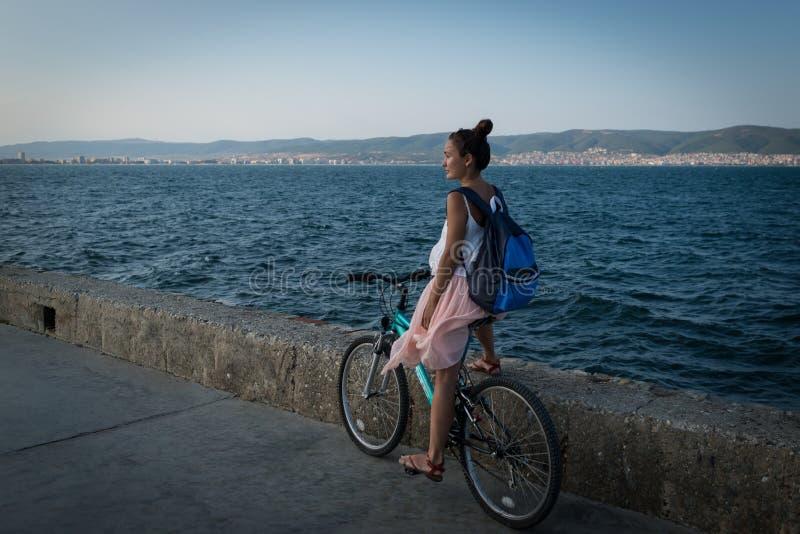De jonge modieuze vrouw in kleding en met rugzak berijdt fiets op promenade stock foto