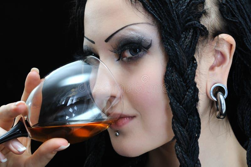 De jonge modieuze vrouw met dreadlocks drinkt rode wijn stock afbeeldingen