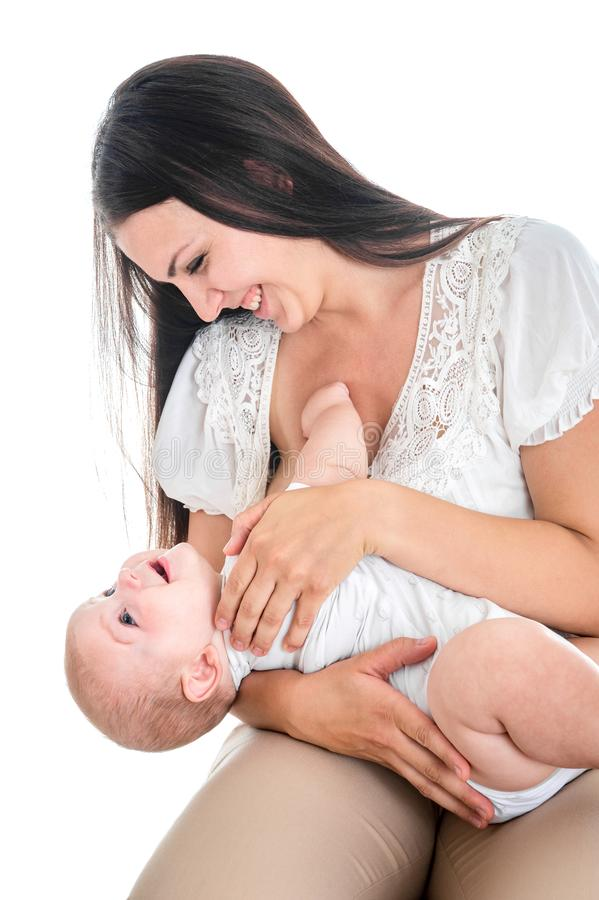 De jonge moeder die haar baby de borst geven, wordt het kind gespeeld en wil geen melk drinken stock afbeeldingen