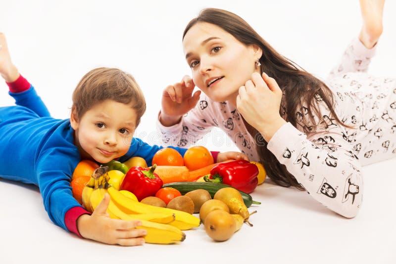 De jonge moeder eet fruit en groenten met haar jonge zoon stock afbeeldingen