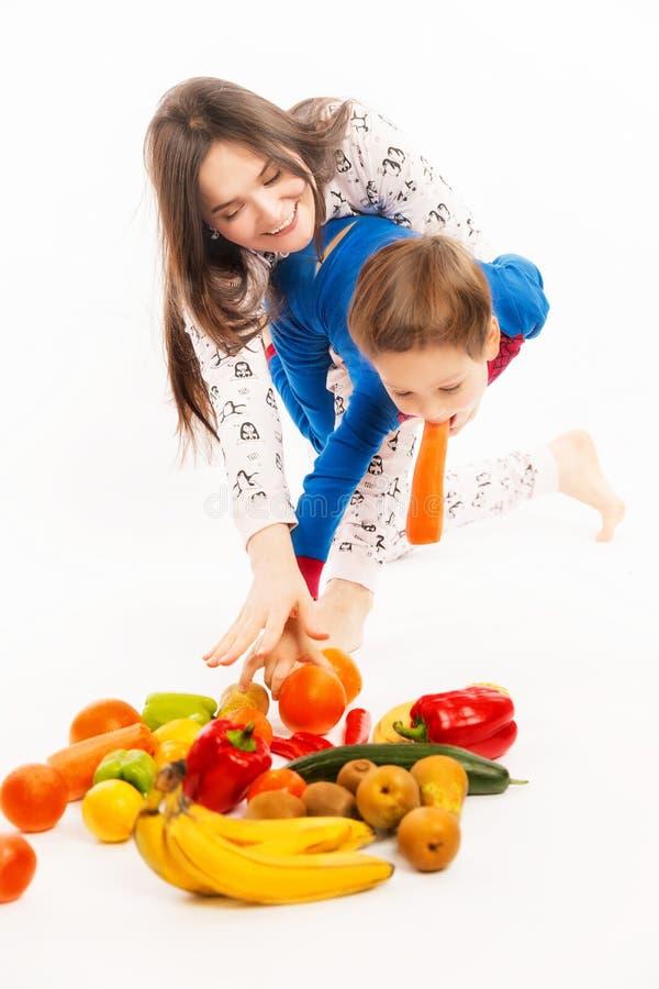 De jonge moeder eet fruit en groenten met haar jonge zoon royalty-vrije stock foto's