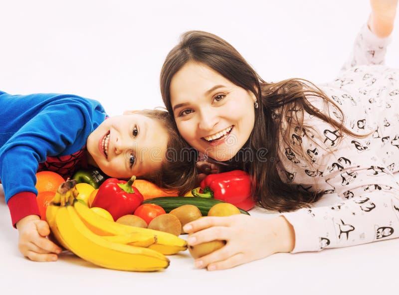 De jonge moeder eet fruit en groenten met haar jonge zoon royalty-vrije stock foto